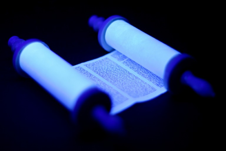 A torah scroll with hebrew text lit with a blue glow