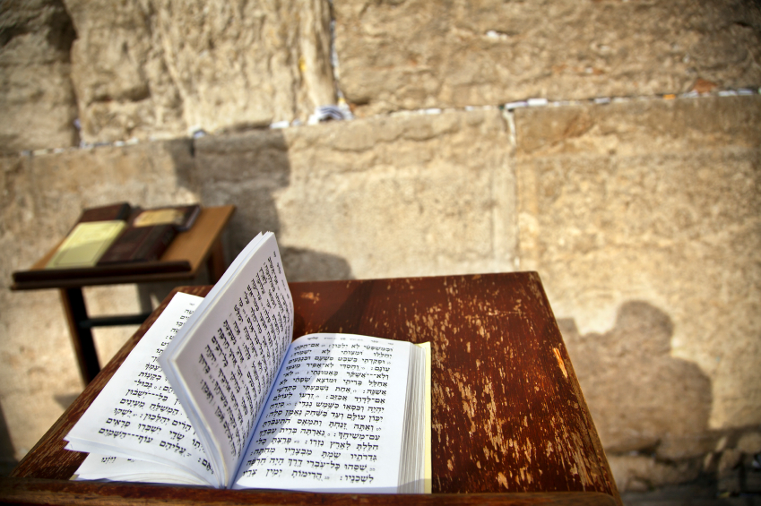 The biblical Book of Psalms opened on one of the pages of the morning prayer, resting on a pedistal . There's also a shadow of a Jewish orthodox man on the wailing wall in the background. Shot in the western wall in the old city of Jerusalem.