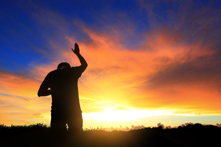Silhouette of man praying with heavenly cloudscape sunset concept for religion, worship, love and spirituality