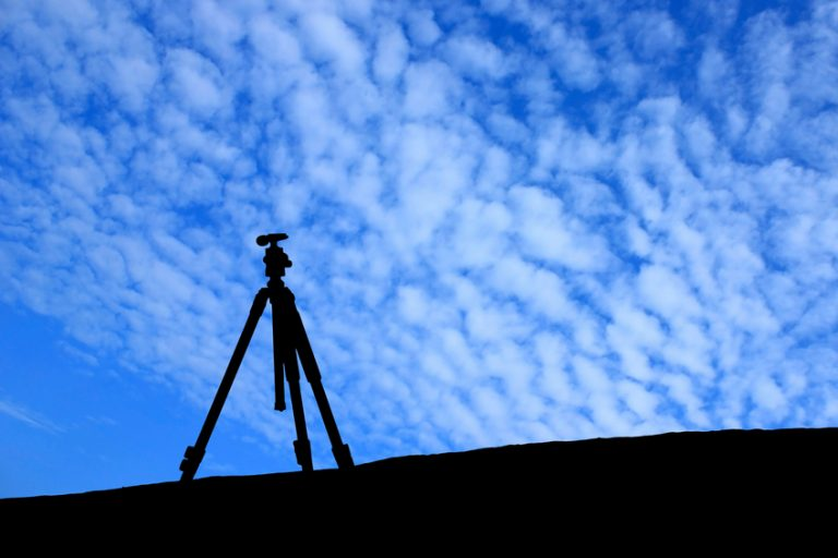 Silhouette of tripod under the blue sky.
