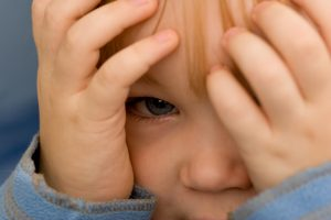 Boy peeking from behind his hands.