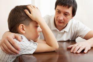 Father comforts a sad child.