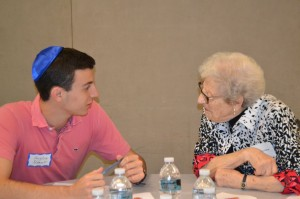Douglas Nabert, 16, an NCSYer from Florida, talks with a woman whose husband survived Auschwitz.