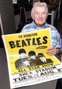 Sid Bernstein holding a Beatles concert poster.